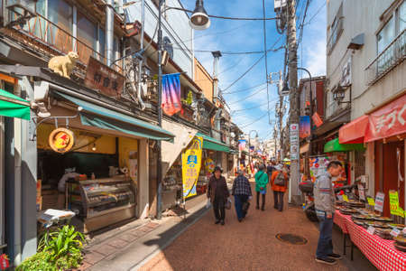 tokyo, japan - april 05 2019: Old-fashioned Yanaka-Ginza shopping street with elderlies pedestrians making shopping at traditional tempura or bento shops adorned with cat statue on the roof.