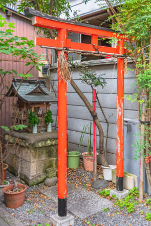 tokyo, japan - march 15 2021: Japanese shintoist red torii gate and small massha wooden altar dedicated to the Inari fox shinto kami god of rice in the neighborhood district of Sumida ward.