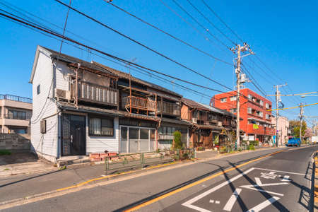 tokyo, japan - march 15 2021: Typical japanese houses from Showa era rehabilitated as Coffee Shop in the downtown rural district of Yanaka and Sendagi with old balconies made in rusty metal.