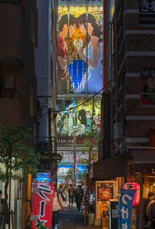tokyo, japan - april 29 2018: Advertising posters of Japanese anime between the skyscrapers of akihabara with ramen noodles restaurant illuminated at night in a narrow street of the electric town.