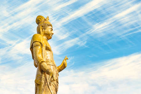 Side view of the Buddhist golden statue of Kishou Kanzeon bodhisattva or kannon bosatsu on a sky background.