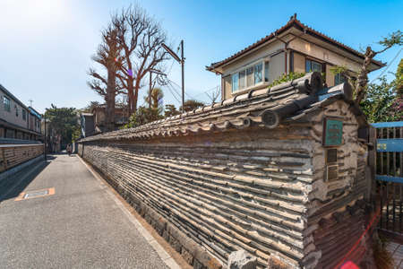 tokyo, japan - march 30 2021: Cob wall called Tuijibei built in a traditional architecture of stacked roof tiles typical of Edo era and classified as cultural heritage of Yanaka district.