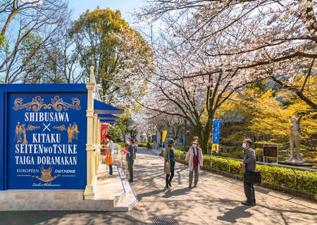 tokyo, japan - march 23 2021: Ticket booth during exhibition dedicated to Shibusawa Eichi in front of the sculpture of Seibo Kitamura in the alley of Asukayama park overlooked by cherry blossoms.