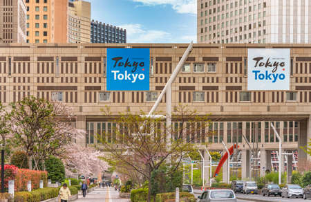 tokyo, japan - march 25 2021: Advertising posters promoting Tokyo city and claiming old meets new the skyscrapers of Tokyo Metropolitan Government Building during spring with cherry blossoms.