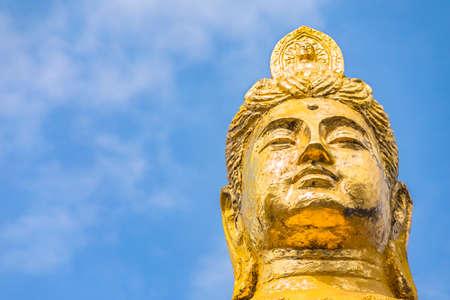 Buddhist golden face of the statue of Kishou Kanzeon bodhisattva known as kannon bosatsu goddess of mercy on a blue sky background.