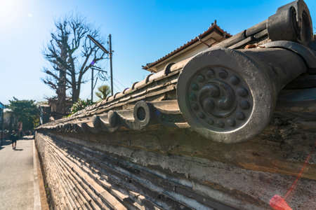 tokyo, japan - april 05 2021: Close up on a traditional Japanese eave-end round tiles adorned with a comma-like swirl tomoe symbol on the Tuijibei cob wall classified as cultural heritage in Yanaka. Sajtókép