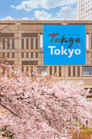 tokyo, japan - march 25 2021: Blossoming cherry blossoms in front of an advertising poster promoting Tokyo city claiming old meets new on the Tokyo Metropolitan Government Building during spring. Sajtókép