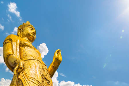 Large golden Buddhist statue taken from below depicting Kishou Kanzeon bodhisattva known as Goddess of Mercy Kannon Bosatsu doing mudra gesture of teaching with hands.