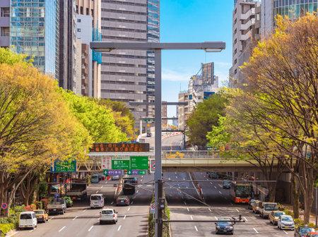 tokyo, japan - april 15 2021: Cars traffic under the Tsunohazu bridge at the intersection of the Kouen street and Minami street of Nishi-Shinjuku leading to the Shutoko Expressway between skyscrapers.