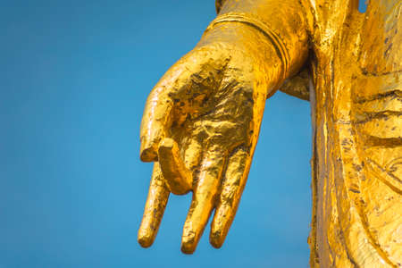 Close up on the hand of a golden Buddhist statue of Goddess of Mercy Kannon Bosatsu depicting a mudra gesture of teaching called dharmachakra with fingers. Stock fotó