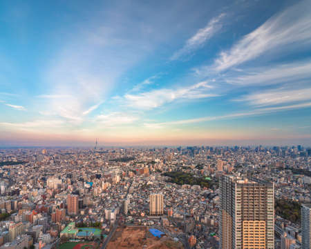 Wide panoramic sunset view of Tokyo city with skyscrapers of East Ikebukuro and the IKE・SUNPARK in construction in foreground and the Japan tallest building skytree tower in background. Stock fotó