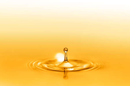 Close up on drop splash of a healthy extra-virgin oil full of oligo elements and vitamins creating circular waves by falling down on the liquid and seamless pure surface shining with golden reflects.