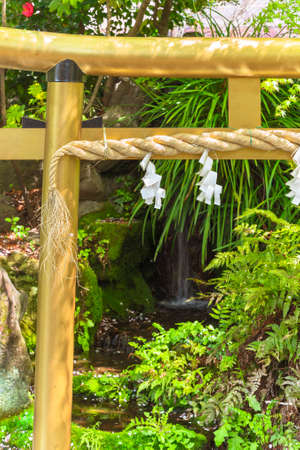 Close up on a Japanese golden gate named torii adorned with a sacred straw rope called shimenawa against a waterfall in a Japanese garden.