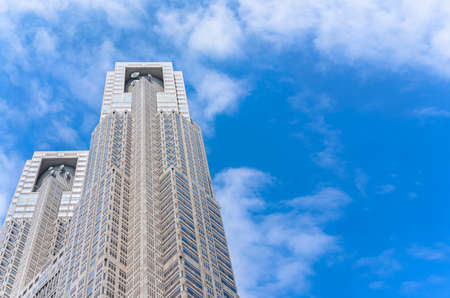 Modern architecture of cuboid columns overlooked by parabolic antennas at top of the towers of the Tokyo Metropolitan Government Building in Shinjuku against a blue sky.