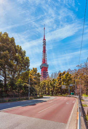 Road curve of the hakusan iwaida tamachi street lined by trees and leading to the Tokyo Tower the tallest lattice tower in Japan inspired by the Eiffel Tower against a blue sky with cirrus clouds.