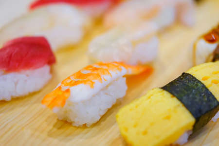 Closeup on Japanese ebi shrimp and tamagoyaki grilled egg sushi with other seafood pieces of rice hand-pressed nigirizushi including ika squid, hotate scallop or maguro tuna.