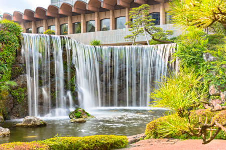 tokyo, japan - july 25 2021: Closeup long exposure on the big waterfall of the Hotel New Otani famous for its Japanese Garden in the kioi district.
