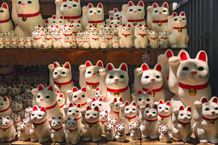 tokyo, japan - july 25 2021: Dozens of kawaii Japanese manekineko cat lucky charms sculptures depicting to the famous beckoning cat offered by buddhist worshipers in the gotokuji zen temple. Editöryel