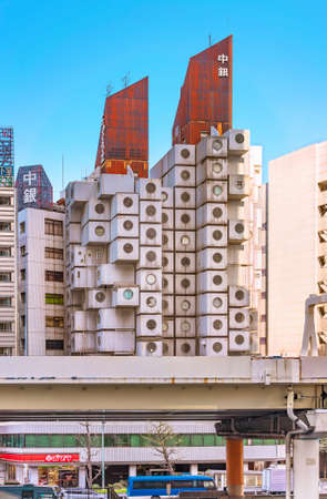 tokyo, japan - july 05 2021: Nakagin Capsule Tower building topped by a rusted corrugated sheet rooftop created in 1972 by Japanese architect Kisho Kurokawa in front of Shuto Expressway in Shimbashi. Editöryel