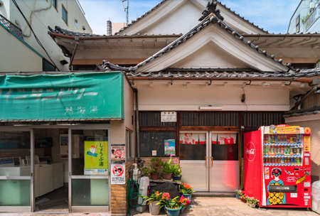 tokyo, japan - july 15 2021: Traditional Japanese bathhouse Atamiyu in Kagurazaka with a beverages vending machine and flowers in front and a coin laundry store with prevention posters beside. Editöryel