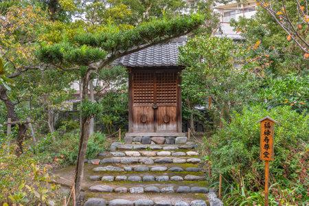 tokyo, japan - november 13 2020: Small shrine with the Japanese name of longevity god Fukurokuju god on a wooden board in the Mukojima-Hyakkaen Gardens dedicated to the seven lucky gods pilgrimage.