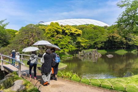 tokyo, japan - May 03 2021: Japanese tourists holding sun umbrellas and walking on the bridge of Koishikawa Korakuen Park along the lake with the Horai island in center and Tokyo Dome in background. Editöryel