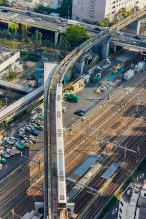 tokyo, japan - april 25 2021: Bird's-eye view of a Yamanote Line train on the tracks of the Hamamatsucho Station overlooked by the aerial Tokyo Monorail Haneda Airport Line and the Shuto expressway. Editöryel
