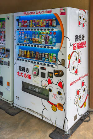 tokyo, japan - march 02 2021: Japanese drinks vending machine covered with advertising stickers of Manekineko lucky cats illustrations in buddhist gotokuji temple known as birthplace of maneki-neko.