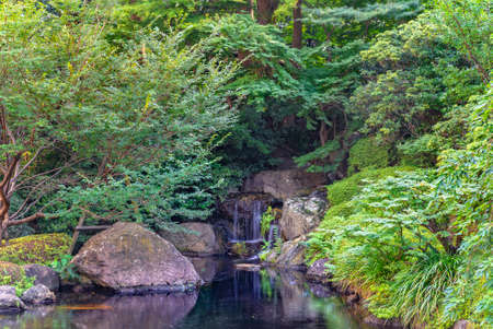 tokyo, japan - july 25 2021: Small waterfall surrounded by rocks and plants in the pond of the Hotel New Otani famous for its Japanese Garden in the kioi district.