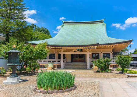 tokyo, japan - july 25 2021: Concrete architecture of the main hall or hondo of buddhist gotokuji zen temple dedicated to Japanese Manekineko cat with a gold bronze octagonal lantern and a flowerbed.