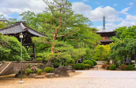 tokyo, japan - june 5 2021: Japanese shoro bell tower and buddhist three-story timber pagoda in the inner garden of the gotokuji zen temple known as birthplace of manekineko cat meaning beckoning cat.
