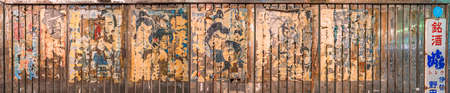 tokyo, japan - july 05 2021: Panorama of aligned japanese yakuza and samurai classic movies posters stuck along the rusted corrugated wall of Yuraku Concourse underpass between Ginza and Hibiya.