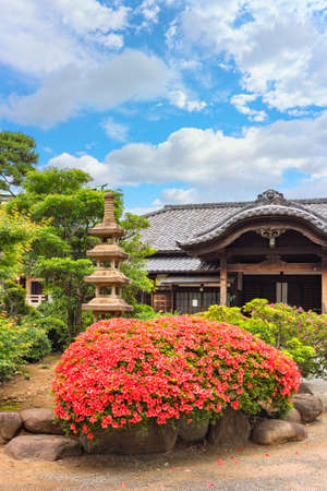 tokyo, japan - june 05 2021: Inner garden of the Buddhist gotokuji zen temple adorned with a pink azalea shrub and a six storied stone pagoda Kuyoto symbol of Buddhist funerals.