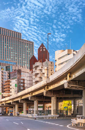 tokyo, japan - july 05 2021: Shuto Expressway in the Shimbashi district with the iconic Nakagin Capsule Tower building topped by a rusted rooftop created in 1972 by Japanese architect Kisho Kurokawa. Editöryel