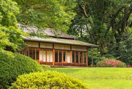 tokyo, japan - june 25 2021: Japanese chashitsu tea room Kakuuntei teahouse used by Meiji emperor for tea ceremony in the Meiji Jingu Inner Garden adorned with azalea Niwaki shrubs.