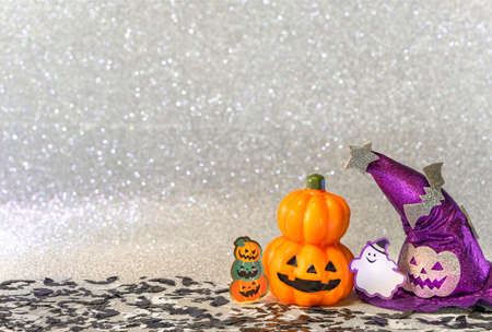 Concept photography depicting an halloween jack o lantern pumpkin head and a purple witches hat with funny ghost smiling and cardboard cutout bats against a glitter silver background of bokeh balls. Stok Fotoğraf