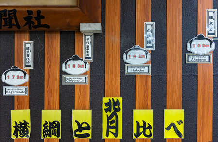 tokyo, japan - august 15 2021: Wall adorned with cardboard cutouts depicting sumotori yokozuna faces to compare the size of famous Japanese professionals sumo wrestlers in the Ryogoku train station. Editöryel