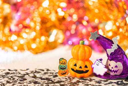 Creative photography depicting an halloween jack o lantern pumpkin head and a purple witches hat with funny ghost smiling and cardboard cutout bats against a colorful background of bokeh balls.