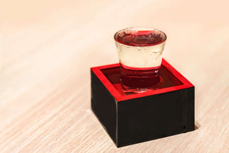 Chilled Japanese rice wine called nihonshu in a transparent overflowing sake-serving shot glass inside a traditional square lacquered wooden box called masu filled to the rim as a sign of prosperity.