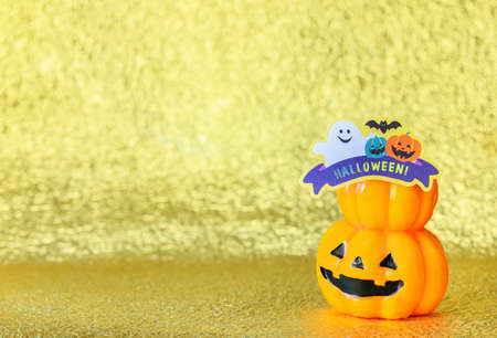Studio photography depicting a smiling halloween jack o lantern pumpkin head with cardboard cutout of a funny ghost and bats with the word Halloween! against a glitter golden background. Stok Fotoğraf