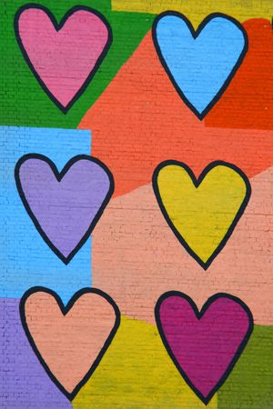 Colorful graffiti spray painted funny hearts on the decorated  brick wall - makes a great background or backdrop Imagens