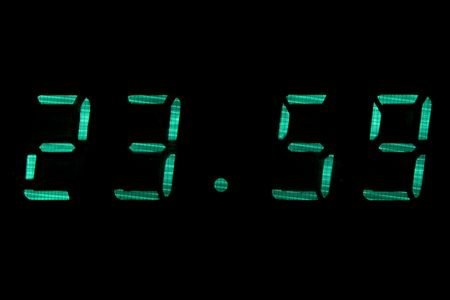 digital clock in green isolated black photo