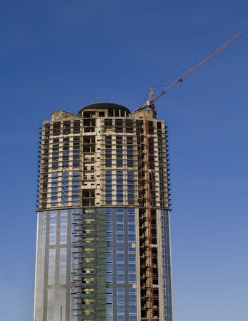 erect: Cranes and building construction of a skyscraper early morning against the dark blue sky Stock Photo