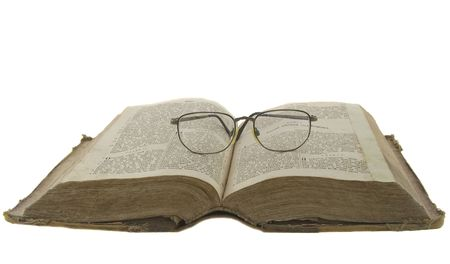 Vintage open book bible open and glasses on it isolated over white photo