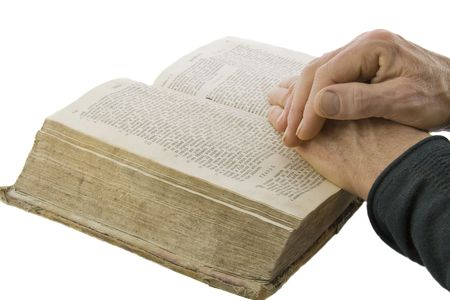 Male hands closed in prayer on an open bible isolated over white photo