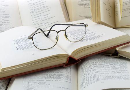 diccionarios: Muchos libros y gafas que le Foto de archivo