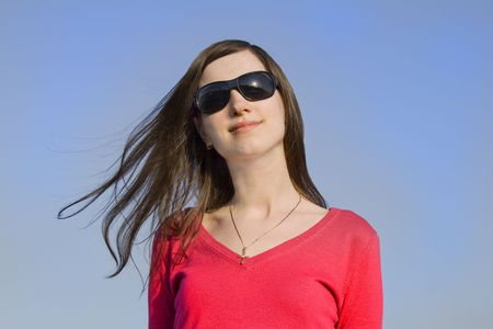 Closeup portrait of a beautiful young woman in sunglasses over big blue sky Stock Photo - 4631393