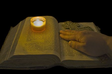 Male hand lies on ancient bible with a big christian cross in the light of a candle over black background Stock Photo - 4631451