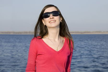 Closeup portrait of a beautiful young woman in sunglasses over big blue sky Stock Photo - 4721881