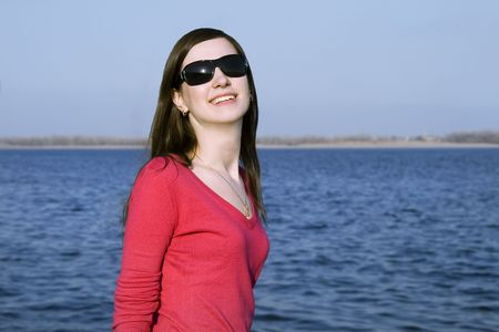 Closeup portrait of a beautiful young woman in sunglasses over big blue sky Stock Photo - 4721884